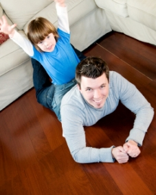 man and child lying on the hardwood floor in a Vancouver home